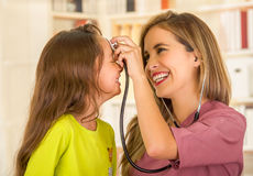 Young pretty girl smiling while a beautiful smiling doctor examining with a stethoscope in her head in a office Stock Photography