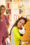 Young pretty girl smiling and hugging her teddy bear in a office background with a burred doctor Stock Images