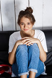 Young pretty girl smiling, sitting on sofa at home. Stock Photos