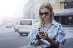 Young pretty girl smoking vipe and serfing in smartphone. City , outdoor. Blonde haired woman using cellphone and electronic cigarette on the background of Stock Images
