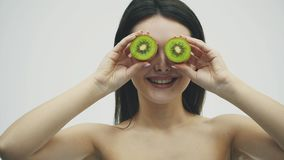 Young pretty girl standing on a white background. During this, at the level of the eye, the kiwi particles are kept in