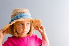 Young pretty girl in straw hat looking away stock photography