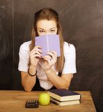 Young pretty girl student in classroom at. Blackboard doing homework Stock Photo