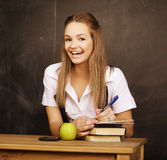 Young pretty girl student in classroom at. Blackboard doing homework Stock Photography