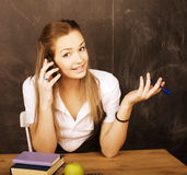 Young pretty girl student in classroom at blackboard. Doing homework Stock Images