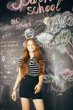 Young pretty girl student in classroom at. Blackboard doing homework, confident teenage Stock Images