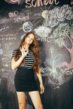 Young pretty girl student in classroom at. Blackboard doing homework, confident teenage Stock Image