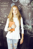 Young pretty girl student in classroom at. Blackboard doing homework, confident teenage Royalty Free Stock Images