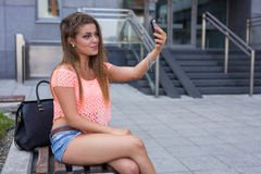 Young pretty girl taking selfie. Urban background. Royalty Free Stock Photo