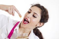 Young pretty girl tasted honey Royalty Free Stock Photos