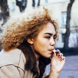 Young pretty girl teenage outside smoking cigarette close up, lo Stock Image