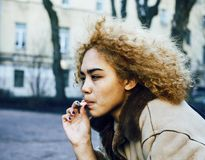 Young pretty girl teenage outside smoking cigarette, looking lik. E modern junky, social issues concept real teen stock images