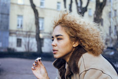 Young pretty girl teenage outside smoking cigarette, looking like real junky, social issues concept Stock Photos