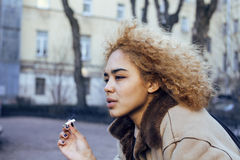 Young pretty girl teenage outside smoking cigarette, looking like real junky, social issues concept Stock Photography