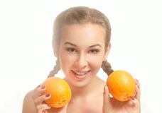 Young pretty girl with two oranges. And pigtails is smiling on a white background Stock Photography
