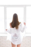 Young pretty girl unclothing a white men's shirt near the window Stock Photos