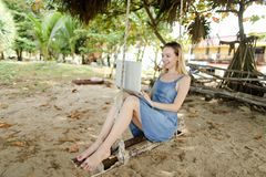 Young pretty girl using laptop and riding on swing on sand. royalty free stock photography