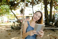 Young pretty girl using tablet and riding swing on sand, wearing jeans sundress. royalty free stock photos