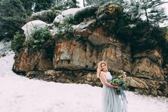 The young pretty girl waits for her lover in the middle of the mountains covered with snow Royalty Free Stock Photos