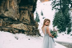 The young pretty girl waits for her lover in the middle of the mountains covered with snow Royalty Free Stock Photo