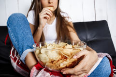 Young pretty girl watching tv, sitting on sofa at home. Young pretty girl eating chips, watching tv, sitting on sofa at home. Copy space Royalty Free Stock Image