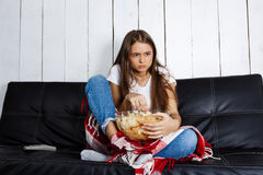 Young pretty girl watching tv, sitting on sofa at home. Royalty Free Stock Photo