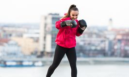Young girl wearing boxing gloves throwing a punch - martial arts Royalty Free Stock Photos