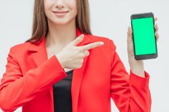 Young pretty pretty girl wearing a red jacket. Stays on a gray background. During this time, holds a black phone. Green