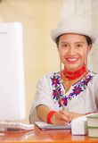 Young pretty girl wearing white shirt with colorful flower decorations and fashionable hat, sitting by desk working Stock Image