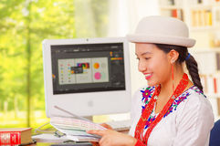 Young pretty girl wearing white shirt and fashionable hat, sitting by computer desk, turning towards camera smiling Royalty Free Stock Photos