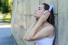 Young pretty girl in white t-shirt listening to music while lean stock photography