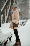 Young pretty girl in winter park stands on snow-covered alley. Telephoto Royalty Free Stock Photo