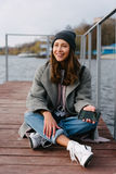 Young pretty girl on wooden bench on old pier. Cute Caucasian model Royalty Free Stock Image