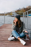 Young pretty girl on wooden bench on old pier. Cute Caucasian model Stock Photography