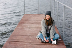 Young pretty girl on wooden bench on old pier. Cute Caucasian model Royalty Free Stock Photo