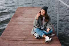 Young pretty girl on wooden bench on old pier. Cute Caucasian model Stock Photo