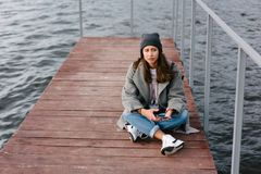 Young pretty girl on wooden bench on old pier. Cute Caucasian model Stock Image