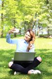 Young pretty girl working on laptop outdoor, lying on grass, caucasian 20 years old Royalty Free Stock Images