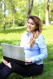 Young pretty girl working on laptop outdoor, lying on grass, caucasian 20 years old. Young pretty girl working on laptop outdoor, lying on grass, caucasian Stock Photos