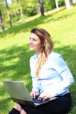 Young pretty girl working on laptop outdoor, lying on grass, caucasian 20 years old. Young pretty girl working on laptop outdoor, lying on grass, caucasian Stock Images