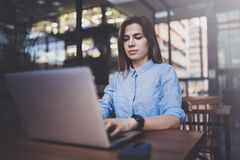 Young pretty girl working on laptop and using mobile smartphone at her workplace at modern office center.Horizontal royalty free stock images