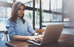 Young pretty girl working on laptop and using mobile smartphone at her workplace at modern office center.Horizontal. Blurred background royalty free stock images