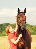 Young pretty girl with yours  horse in field Royalty Free Stock Images