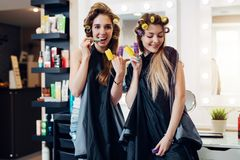 Young pretty girls in capes with hair curlers goofing around in beauty salon. Girlfriends showing devil horn and piece stock photography