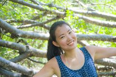 Young pretty and happy Asian Chinese woman taking a walk excursion trip on tropical mountain enjoying nature smiling cheerful in h. Oliday vacation travel and Royalty Free Stock Images