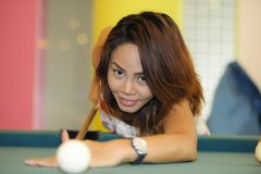 Young pretty and happy Asian girl playing snooker holding stick at pool table in night club or bar. Wearing sexy dress Stock Photography