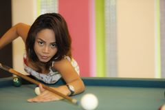 Young pretty and happy Asian girl playing snooker holding stick at pool table in night club or bar. Wearing sexy dress Stock Images