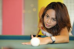 young pretty and happy Asian girl playing snooker holding stick at pool table in night club or bar Stock Photos