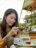 Young pretty and happy Asian Korean travel blogger woman taking picture with mobile phone of beautiful breakfast table at outdoors stock image