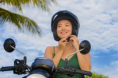 Young pretty happy and cute Asian Chinese woman adjusting motorcycle helmet riding on scooter motorbike isolated on a blue sky in. Safe bike ride safety and Royalty Free Stock Photo